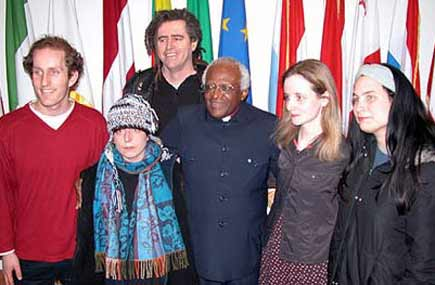 Damien Moran at left stands with his fellow Shannon Airport defendants and Archbishop Desmond Tutu.